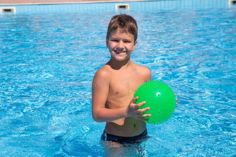 Urocza chłopiec bawić się z piłką w basenie obraz stock