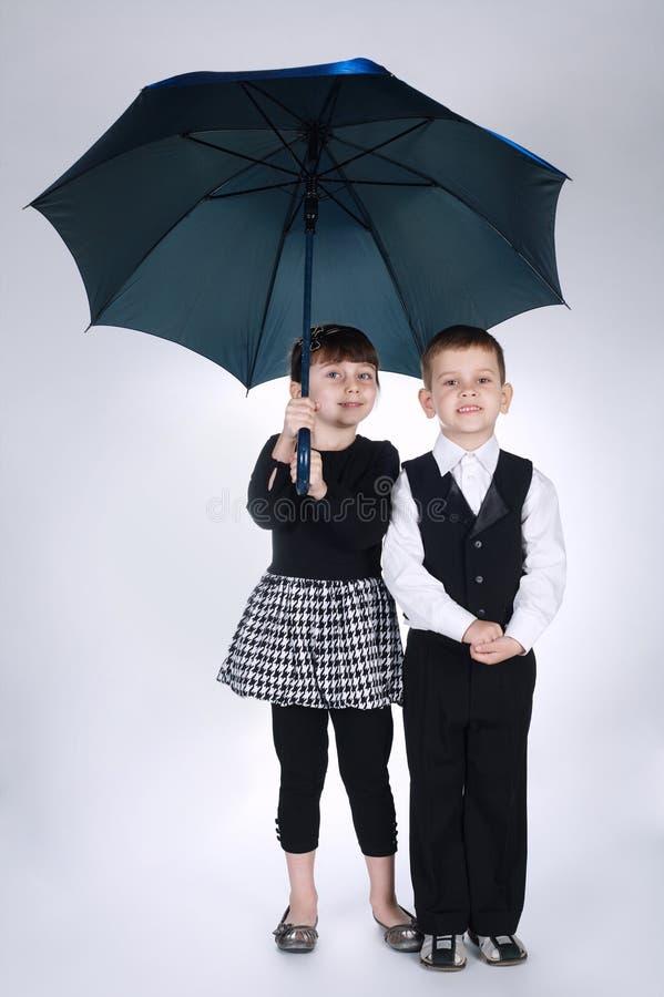 Urocza chłopiec i dziewczyny pozycja pod parasolem zdjęcia stock