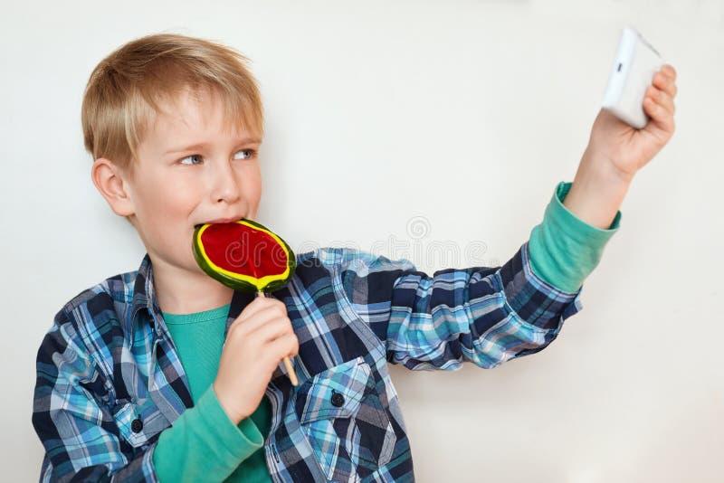Urocza chłopiec liże dużego kolorowego lizaka i robi selfie jego mądrze telefonem odizolowywającym na białym tle Modny k zdjęcie royalty free