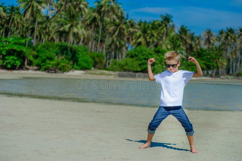 Urocza chłopiec ma zabawę na tropikalnej plaży Biała koszulka, ciemni spodnia i okulary przeciwsłoneczni, Bosy na białym piasku zdjęcia stock