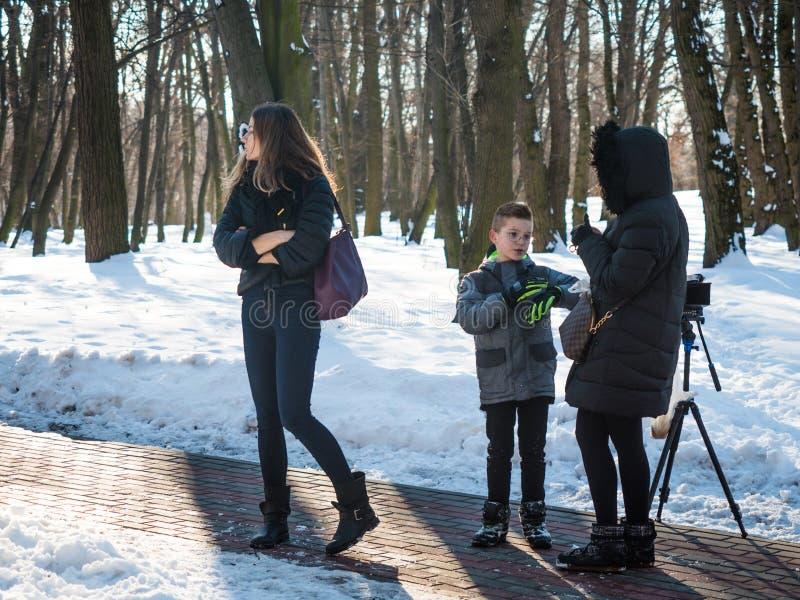 Urocza chłopiec modela rozmowa z producentem w zima parku, zakulisowym obraz stock