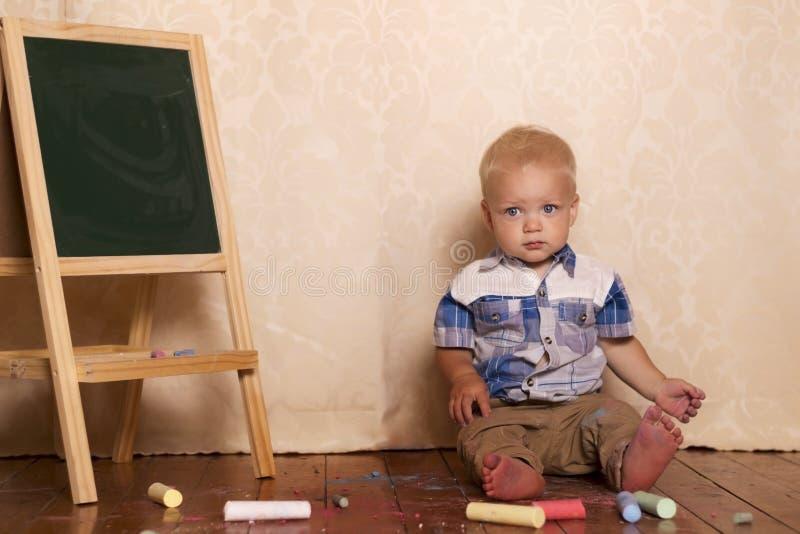 Urocza chłopiec siedzi blisko rysownicy Śliczny berbeć wśród kredy dla rysować kamerę i patrzeć zdjęcie royalty free