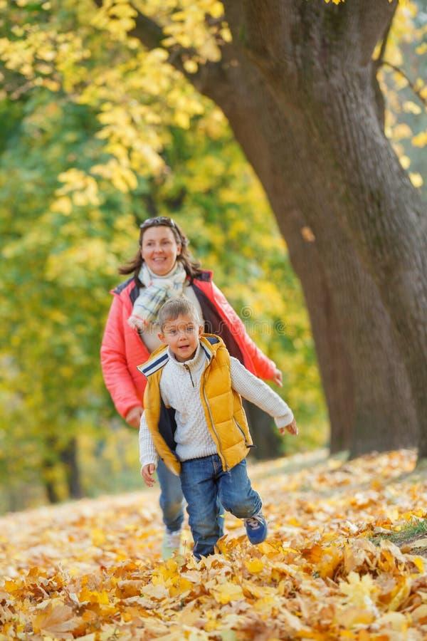 Urocza chłopiec z jego matką w jesień parku obrazy royalty free