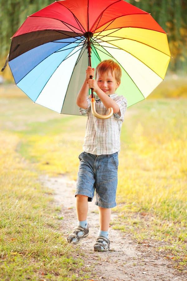Urocza chłopiec z kolorowym parasolem zdjęcia stock