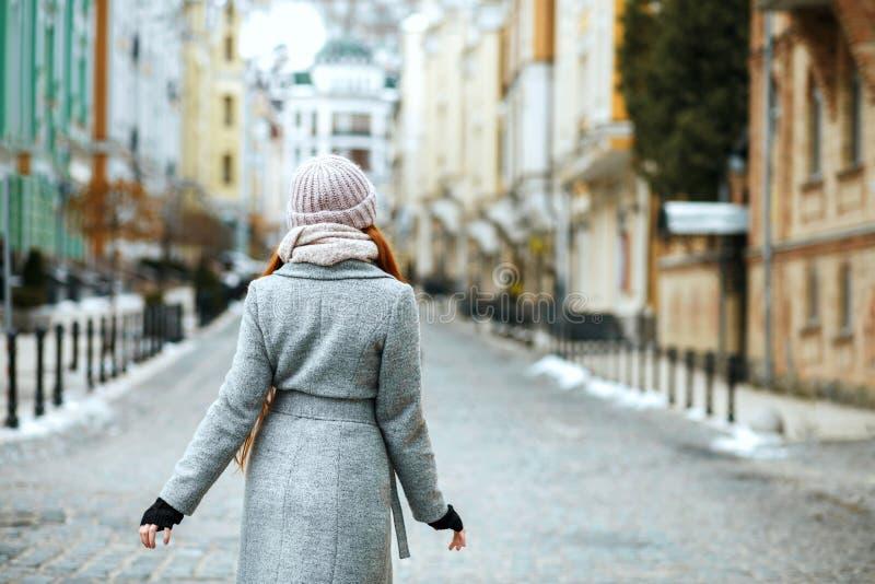 Urocza czerwieni głowy dziewczyna jest ubranym zimy nakrętkę pozuje przy c żakiet i obrazy royalty free