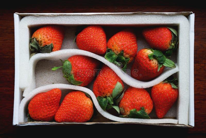 Urocza czerwona świeża dojrzała truskawka w białym pakunku na drewnianym stole, kopii przestrzeń obraz stock