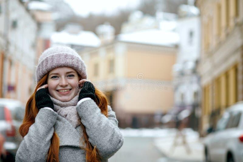 Urocza czerwona z włosami kobieta jest ubranym ciepłej zimy odzieżowego odprowadzenie fotografia royalty free