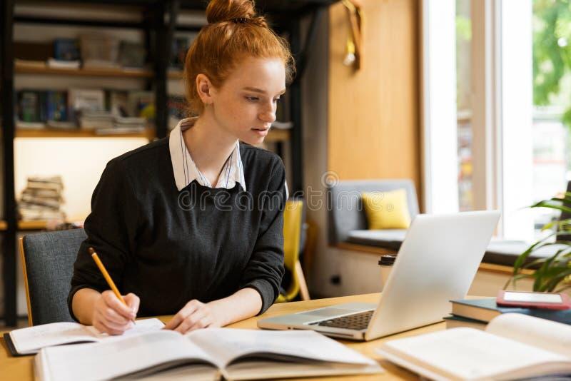 Urocza czerwona z włosami nastoletnia dziewczyna używa laptop obraz stock