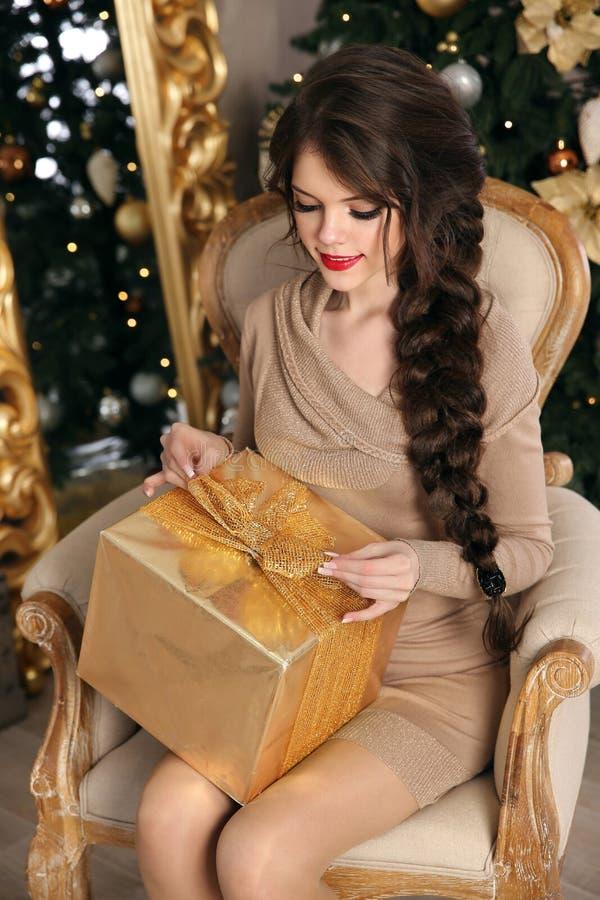 Urocza dosyć nastoletnia dziewczyna z prezenta pudełkiem nad Bożenarodzeniowym backgroun fotografia royalty free
