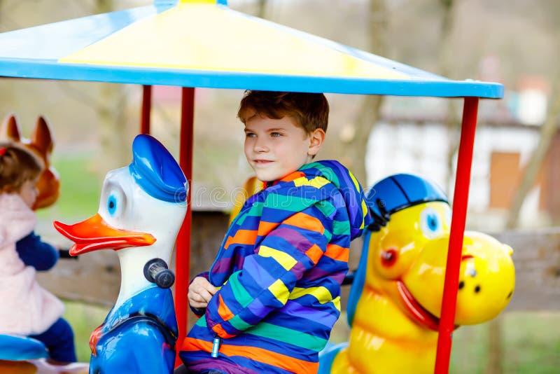 Urocza dzieciak chłopiec jazda na zwierzęciu na ronda carousel w parku rozrywkim Szczęśliwy zdrowy dziecko w wieku szkolnym ma za obraz stock