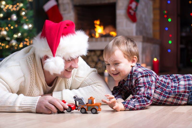 Urocza dzieciak chłopiec, ojciec bawić się z samochodami i bawimy się w domu w christmastime Szczęśliwy dziecko ma zabawę z preze obraz stock