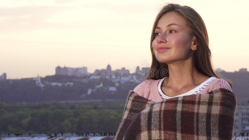 Urocza dziewczyna chuje za dywanikiem i cieszy się widok od dachu fotografia stock
