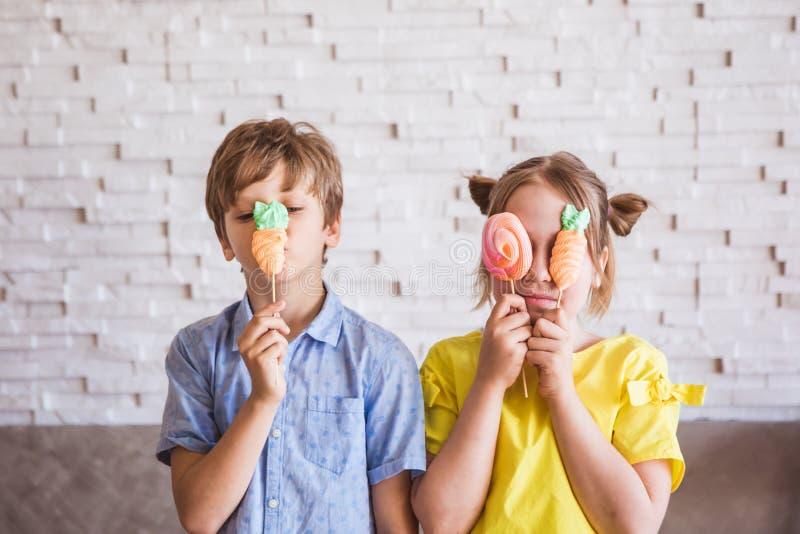Urocza dziewczyna i ch?opiec trzyma kolorowe s?odkie bezy na kiju na Wielkanocnym dniu zdjęcie stock