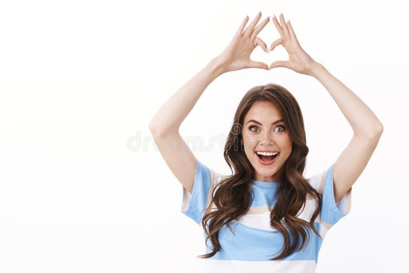 Urocza dziewczyna, jak nowy, fajny sklep, podnieście ręce nad głowę, radośnie pokazując miłość serca zdjęcie royalty free