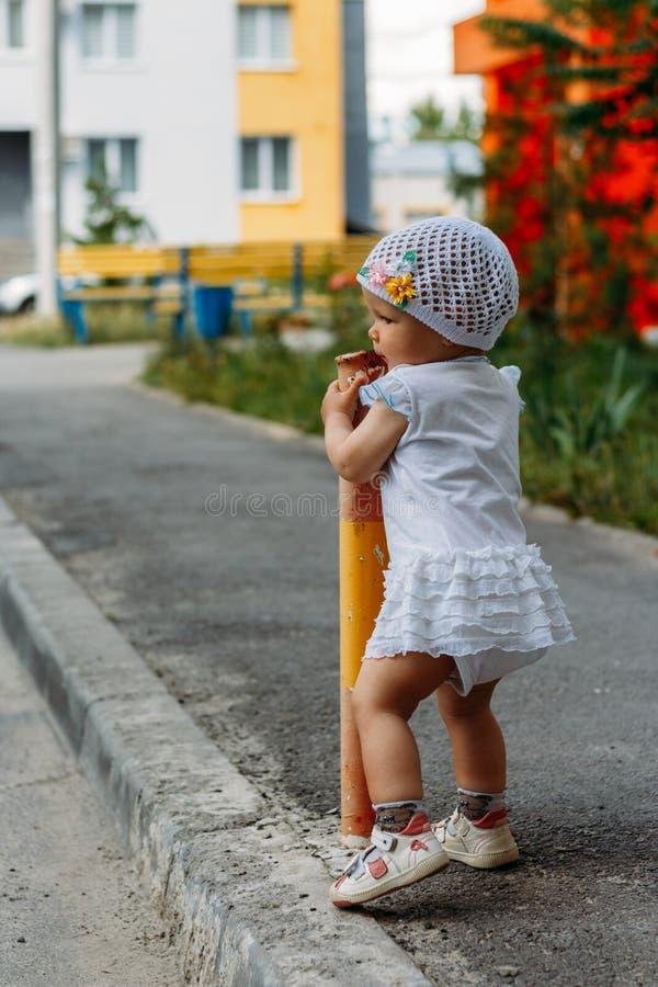 Urocza dziewczyna ma zabawę na letnim dniu troszkę dziewczyna stojaki na przemiany ścieżce i przylegają ogrodzenie, drymba fotografia royalty free