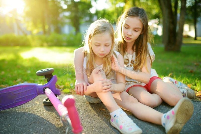 Urocza dziewczyna pociesza jej małej siostry po tym jak spadał z jej hulajnoga przy lato parkiem Dziecko dostaje skaleczenie podc zdjęcia royalty free