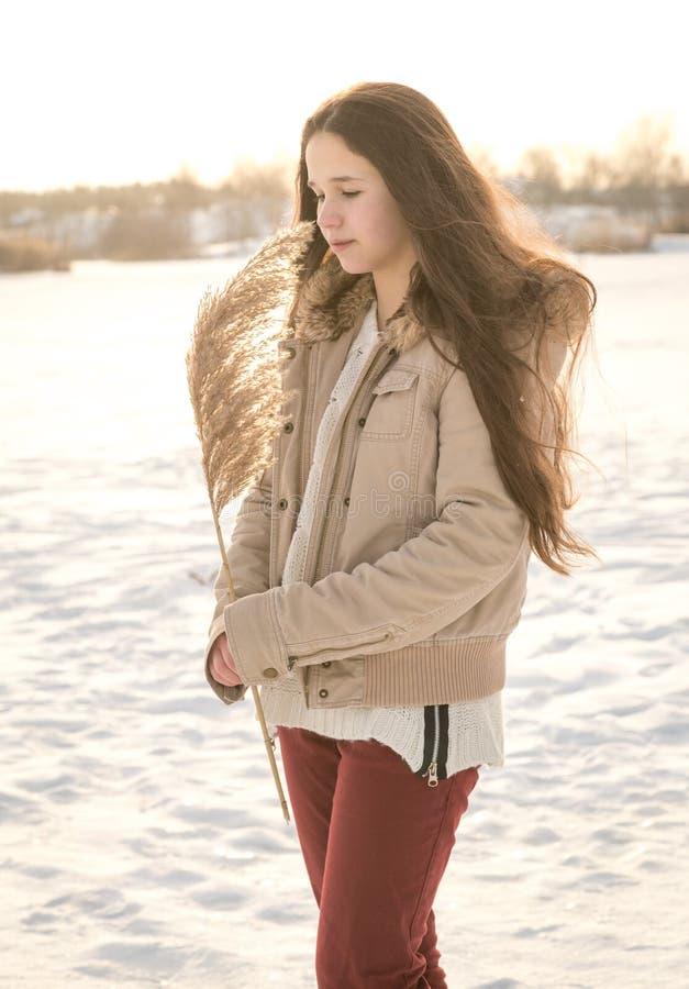 Urocza dziewczyna trzyma trzcinowego trzon przy zima krajobrazem obraz stock
