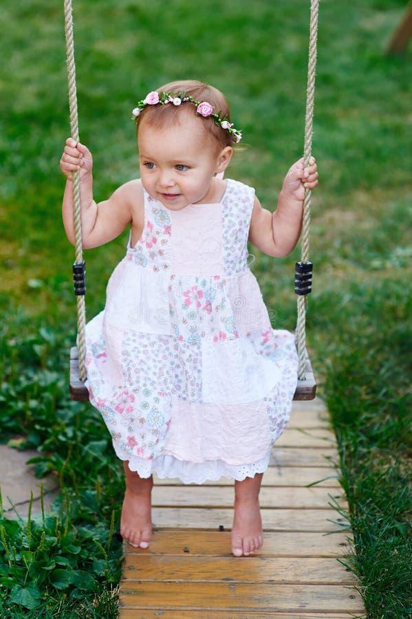 Urocza dziewczynka cieszy się huśtawkową przejażdżkę na boisku w parku obraz stock