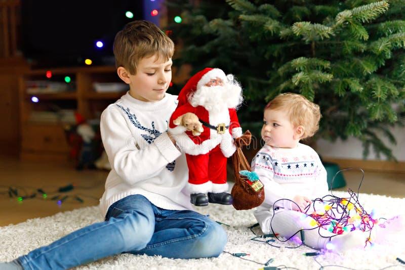 Urocza dziewczynka i brat trzyma kolorowych światła girlandy i zabawkę Święty Mikołaj w ślicznych rękach Małe dzieci, dzieciak fotografia royalty free