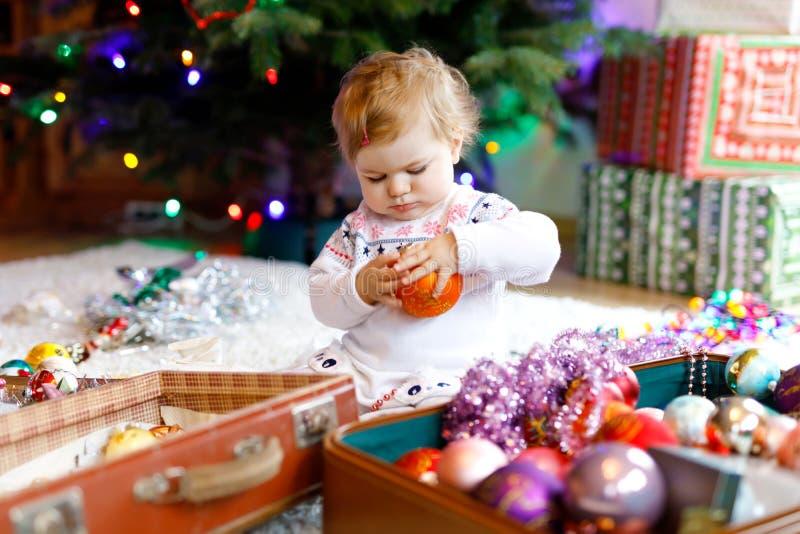 Urocza dziewczynka trzyma kolorowego rocznika xmas bawi się i piłka w ślicznych rękach Małe dziecko w świątecznym odziewa dekorow zdjęcia royalty free