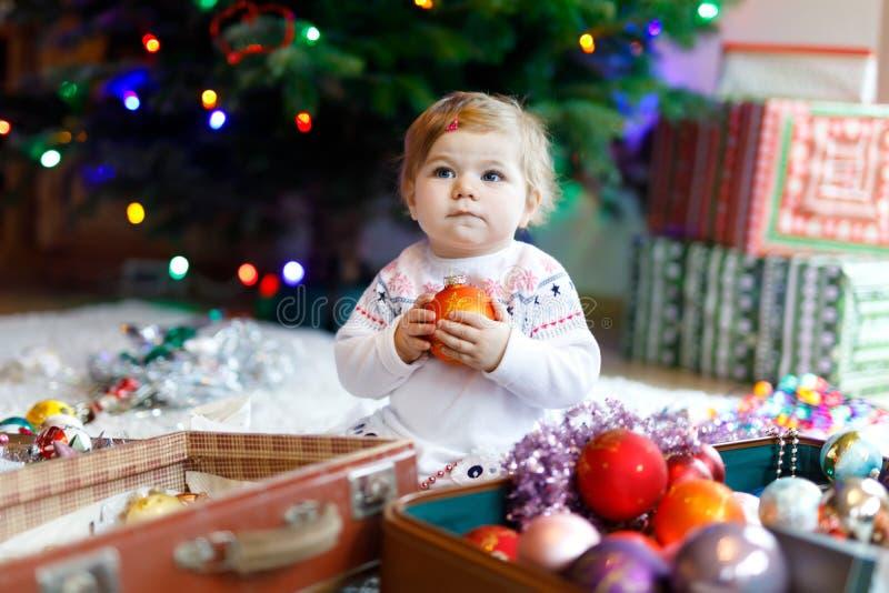 Urocza dziewczynka trzyma kolorowego rocznika xmas bawi się i piłka w ślicznych rękach Małe dziecko w świątecznym odziewa dekorow obraz stock