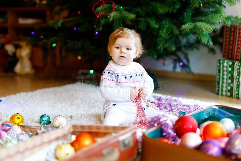 Urocza dziewczynka trzyma kolorowego rocznika xmas bawi się i piłka w ślicznych rękach Małe dziecko w świątecznym odziewa dekorow zdjęcia stock