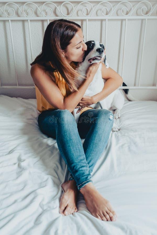 Urocza kobieta całuje labradora szczeniaka w łóżku Labradora szczeniak jest w ona rękami obraz royalty free