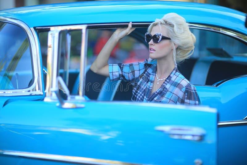 Urocza kobieta Pozuje Wokoło rocznika samochodu i i zdjęcia royalty free