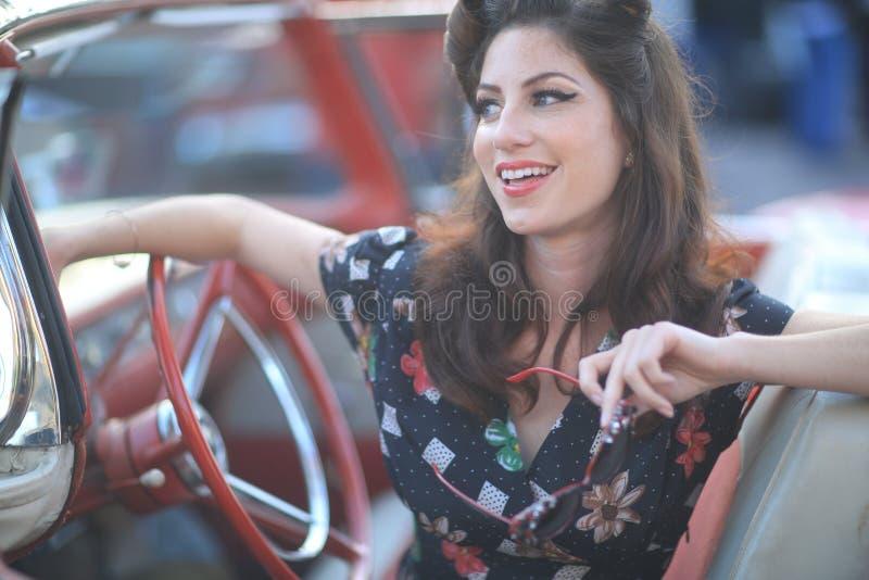 Urocza kobieta Pozuje Wokoło rocznika samochodu i i zdjęcia stock
