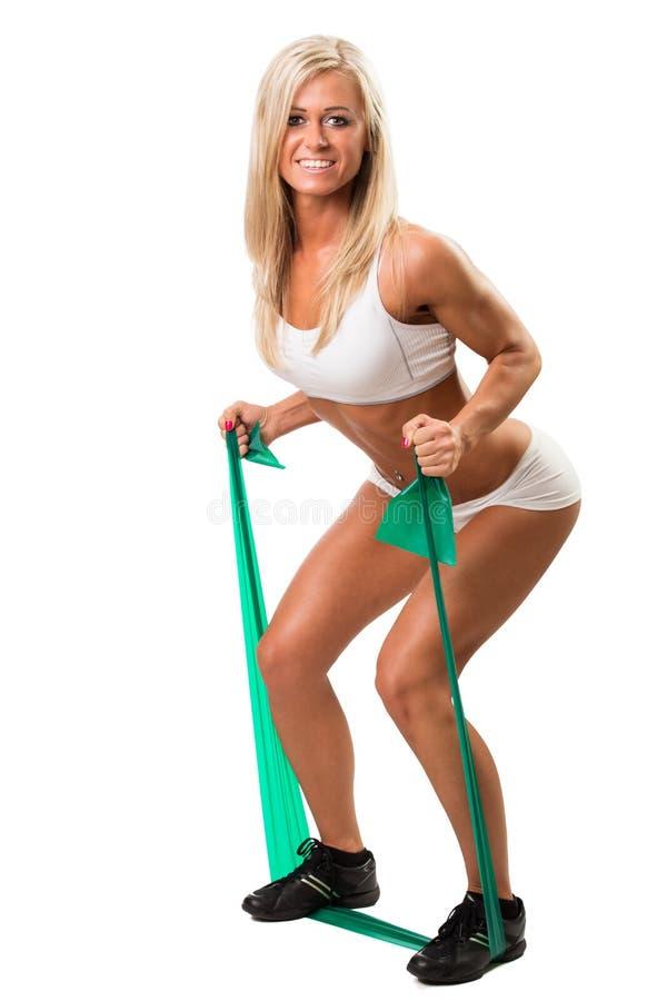 Urocza kobieta robi sprawności fizycznej ćwiczy z gumowym zespołem w biel sukni zdjęcie stock