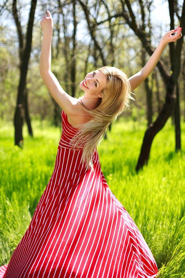 Urocza lato młoda kobieta w długiej czerwieni sukni zdjęcie stock