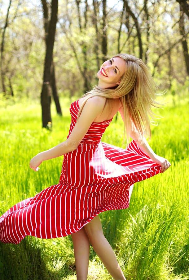 Urocza lato młoda kobieta w długiej czerwieni sukni zdjęcie royalty free