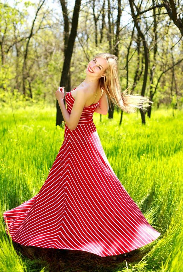 Urocza lato młoda kobieta w długiej czerwieni sukni obrazy stock