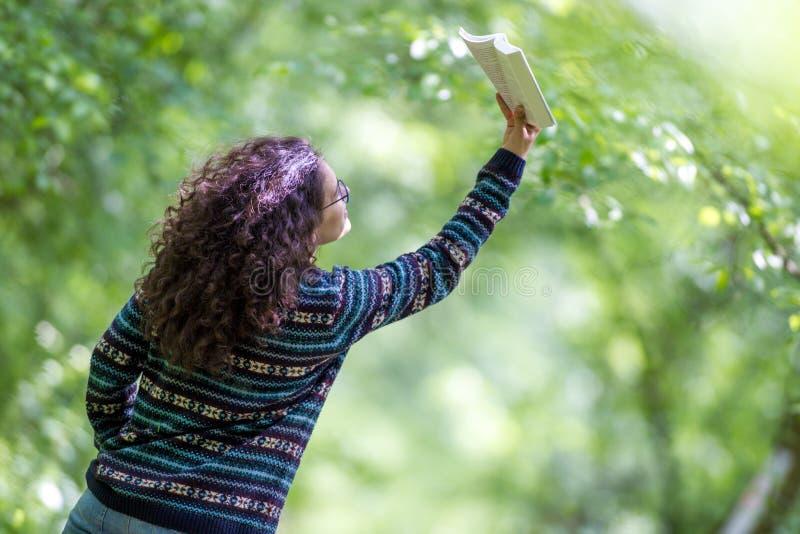 Urocza młoda brunetki kobieta czyta książkę w parku obraz stock