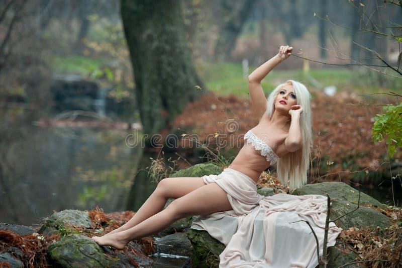 Urocza młoda dama siedzi blisko rzeki w zaczarowanych drewnach Zmysłowa blondynka z biel ubraniami pozuje provocatively w jesienn zdjęcie stock