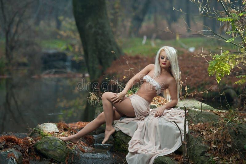 Urocza młoda dama siedzi blisko rzeki w zaczarowanych drewnach Zmysłowa blondynka z biel ubraniami pozuje provocatively w jesienn zdjęcia stock