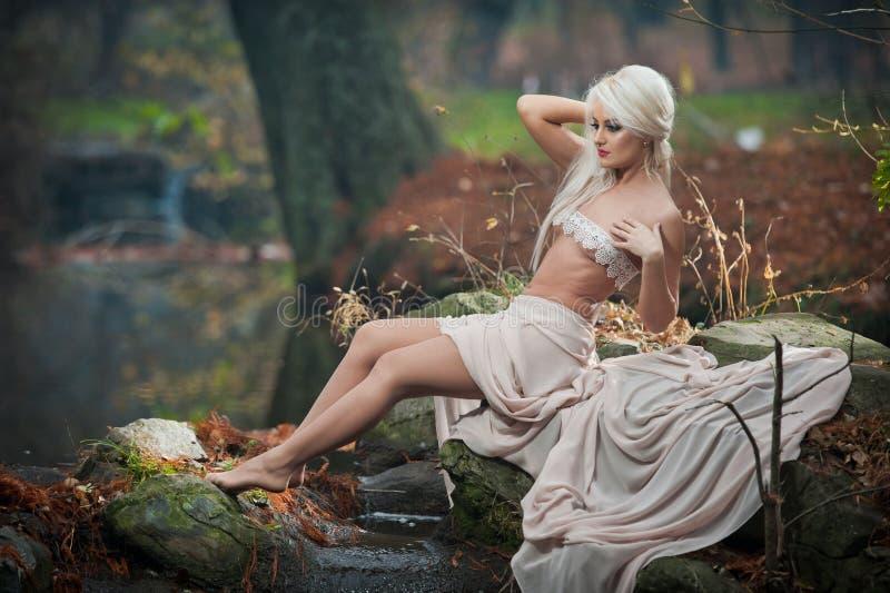 Urocza młoda dama siedzi blisko rzeki w zaczarowanych drewnach Zmysłowa blondynka z biel ubraniami pozuje provocatively w jesienn zdjęcie royalty free