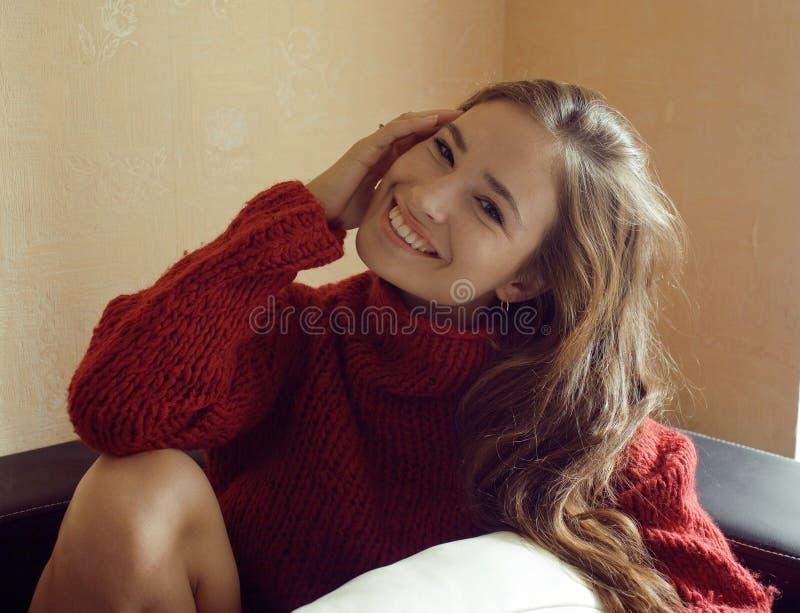 Urocza młoda kobieta ono uśmiecha się w pulowerze w domu obraz stock