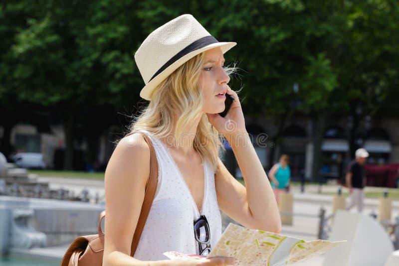 Urocza młoda kobieta opowiada na telefonie komórkowym w kapeluszu fotografia stock