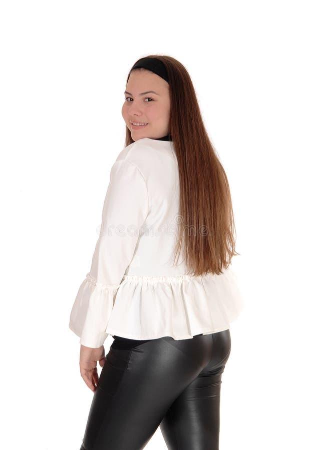 Urocza młoda nastoletniej dziewczyny pozycja od plecy, ono uśmiecha się obraz royalty free