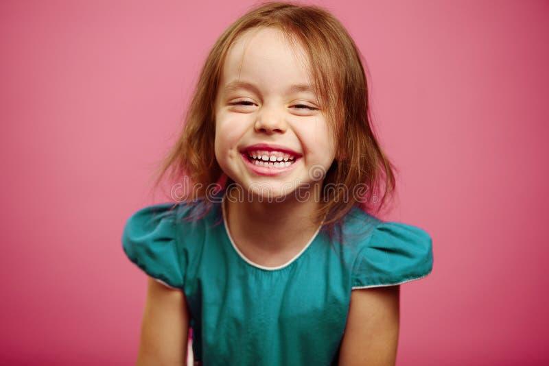 Urocza mała dziewczynka śmia się na menchiach isoalted zdjęcie royalty free