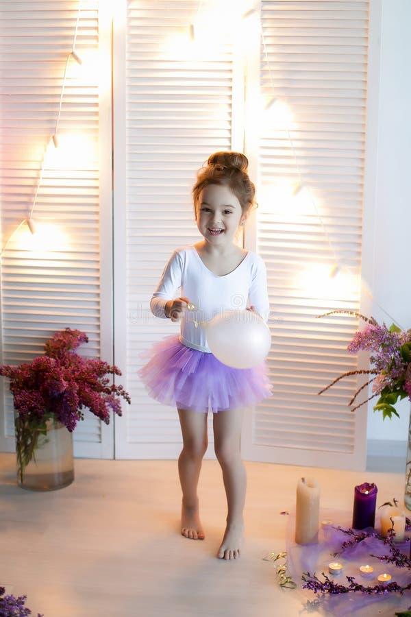 Urocza mała dziewczynka ubierał jako balerina w spódniczka baletnicy, wiąże jej baletniczych kapcie obrazy royalty free
