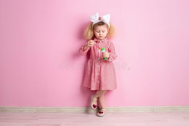 Urocza mała dziewczynka w pasiastego bielu królika, czerwieni i sukni ucho na jej głowie stoi przeciw a i nadyma mydlanych bąble zdjęcia royalty free