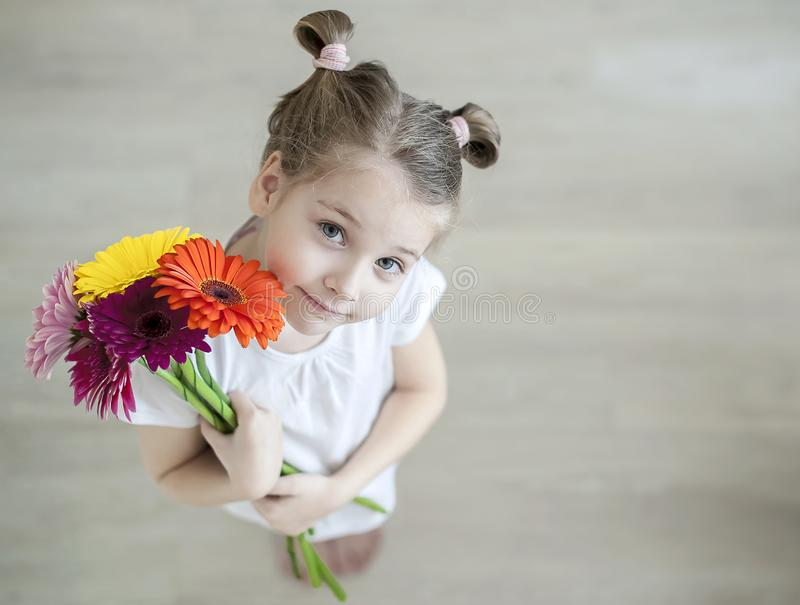 Urocza mała dziewczynka z ślicznym uśmiechu i twarzy mienia wyrażeniowym bukietem menchie, purpury, kolor żółty, pomarańczowe ger obraz stock