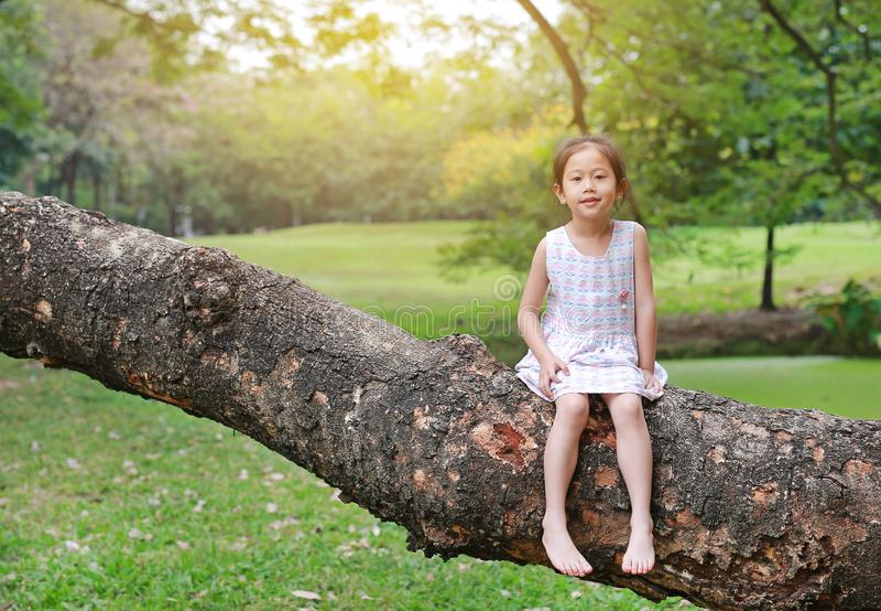 Urocza małe dziecko dziewczyny wspinaczka i odpoczywać na dużym drzewnym bagażniku w ogródzie plenerowym zdjęcia royalty free