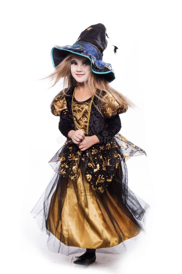 Urocza mała blond dziewczyna jest ubranym czarownicy kostiumowy ono uśmiecha się przy kamerą halloween czarodziejka bajka Pracown obrazy stock