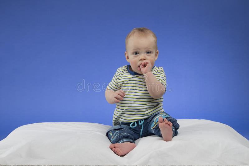 Urocza mała chłopiec, siedzi na białej koc, studio strzał na błękitnym tle, zdjęcie stock