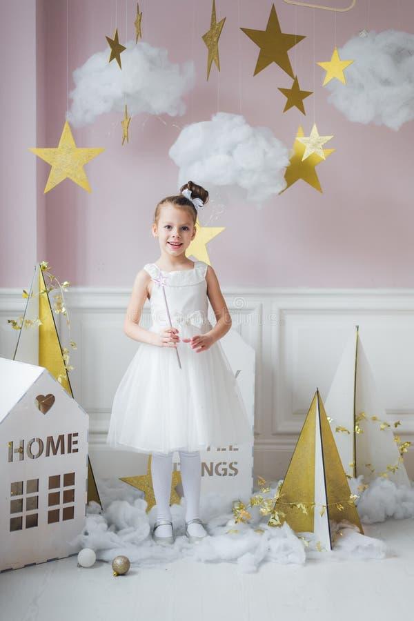 Urocza mała czarodziejska dziewczyna z magiczną różdżką przy boże narodzenie dekoracjami indoors fotografia royalty free