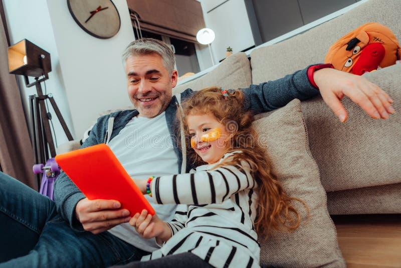 Urocza mała długowłosa dziewczyna i jej ojciec w sportswear patrzeje radosny obraz stock