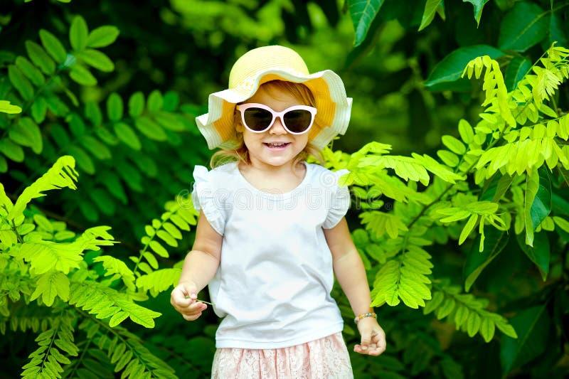 Urocza mała dziewczynka śmia się w łące - szczęśliwa dziewczyna zdjęcia stock